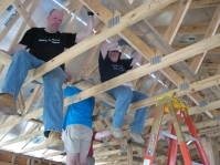 Picture of building crew sitting on new roof beams.